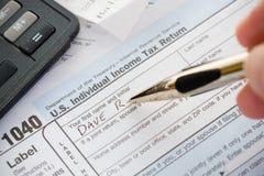 Belastingen: Het schrijven Naam op Belastingaangifte 1040 Royalty-vrije Stock Afbeeldingen
