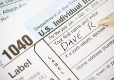 Belastingen: Het schrijven Naam op 1040 Belastingsvorm Stock Foto's