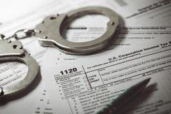 Belastingontwijkingsconcept - belastingsvorm 1120 en handcuffs royalty-vrije stock foto