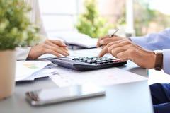 Belastingsaccountants die met documenten werken stock afbeeldingen