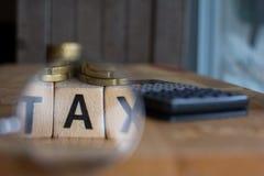 Belastingsconcept met houten blok op gestapelde muntstukken, calculator op de achtergrond royalty-vrije stock afbeeldingen