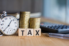 Belastingsconcept met houten blok op gestapelde muntstukken, calculator op de achtergrond stock afbeeldingen