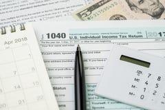 Belastingstijd in April-concept, pen op de individuele inkomstenbelasting van de 1040 V.S. Stock Foto's