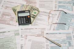 1040 belastingsvorm met calculator, pen en dollar Royalty-vrije Stock Foto's