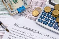 1040 belastingsvorm met geld, pen Stock Fotografie