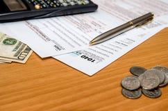 1040 belastingsvorm met ons muntstuk en dollar, calculator, pen Stock Foto