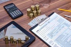 1040 belastingsvorm met tablet, geld, pen Stock Afbeeldingen