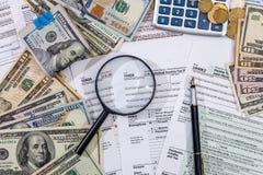 1040 belastingsvorm met vergrootglasdollars, pen en calculator Royalty-vrije Stock Foto's