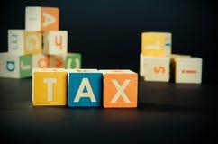 Belastingswoord met kleurrijke blokken Stock Foto's