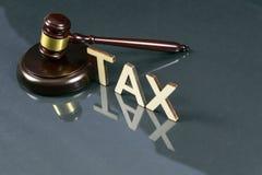 Belastingwetgevingconcept Word BELASTING met hamer en geld op de lijst royalty-vrije stock foto