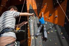 Belayer обеспечивающ альпиниста на стене утеса внутри помещения Стоковое Изображение RF