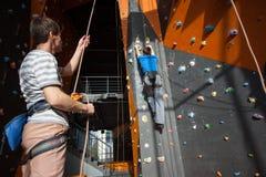 Belayer обеспечивающ альпиниста на стене утеса внутри помещения Стоковая Фотография RF