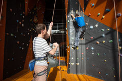 Belayer insuring the climber on rock wall indoors Royalty Free Stock Photography