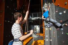 Belayer insuring the climber on rock wall indoors Stock Photos