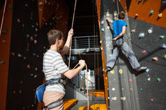 Belayer insuring the climber on rock wall indoors Stock Image