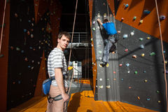 Belayer insuring the climber on rock wall indoors Royalty Free Stock Image