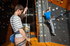 Belayer insuring the climber on rock wall indoors Royalty Free Stock Photos