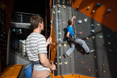 Belayer insuring the climber on rock wall indoors Stock Photography