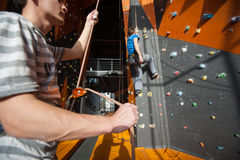Belayer insuring the climber on rock wall indoors Royalty Free Stock Images