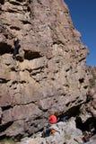Belayer onder klimmer op muur Stock Foto's