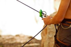 Belayer with the rope and carabines Stock Photo