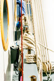 Belayingl pins and window or porthole on a tall ship. Coiled rope lines stored on belaying pins on a sailing vessel Stock Photos