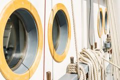 Belayingl pins and window or porthole on a tall ship. Coiled rope lines stored on belaying pins on a sailing vessel Royalty Free Stock Photo