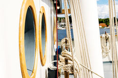 Belayingl pins and window or porthole on a tall ship. Coiled rope lines stored on belaying pins on a sailing vessel Stock Image