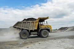 BelAZ卡车运输在土路的矿石 图库摄影
