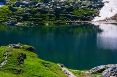 Belea lake in Fagarasan mountains of Romania. Beautiful nature summer scenery with grassy slopes, rocky cliffs and some snow Royalty Free Stock Photography