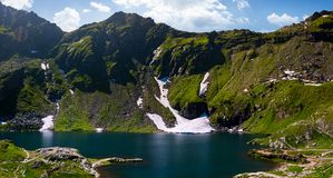 Belea lake in Fagarasan mountains of Romania. Beautiful nature summer scenery with grassy slopes, rocky cliffs and some snow Royalty Free Stock Photo