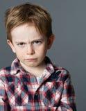 Beledigd jong en kind die uitdrukkend jong geitjewoede mokken pruilen royalty-vrije stock foto