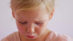 Beledigd meisje op een witte achtergrond Droevig portret van blondekind stock videobeelden