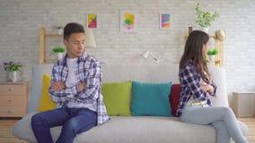 Beledigde Aziatische echtgenoot en vrouwenzitting afzonderlijk op de laag die elkaar negeren stock video