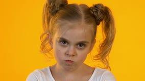 Beledigde weinig kind die boos camera onderzoeken tegen oranje gril als achtergrond stock videobeelden