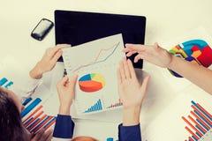 Beleggingsadviseur die bedrijf jaarlijks financieel verslag analyseren Handen met grafiekendocumenten royalty-vrije stock afbeelding