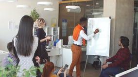 Belegschaftsmitglieder sind, betrachtend stehend und Afro-Partner, der Plan darstellt stock footage