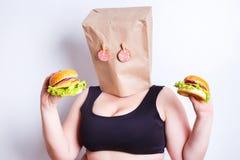 Beleibte fette Frau mit einer Papiertüte auf ihrem Kopf mögen eine Maske mit e stockbild