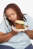 Beleibte Frau, die Burger betrachtet Stockbilder