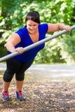 Beleibte Frau, die den Sport draußen ausdehnt in Park tut Lizenzfreies Stockbild