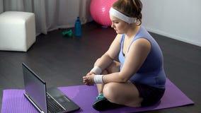 Beleibte Frau, die on-line-Videos von effektiven Ausbildungsmethoden auf ihrem Laptop aufpasst stockfoto