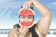Beleibte Frau mit Wassermelone auf Strand Stockfotos