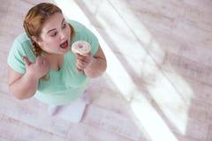 Beleibte junge Frau, die Bonbons isst Lizenzfreie Stockbilder