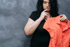 Beleibte schüchterne Frau, die zögert, vibrierendes Hemd zu tragen stockfoto