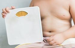 Beleibter fetter Junge, der Gewichts-Skala hält Lizenzfreie Stockfotos