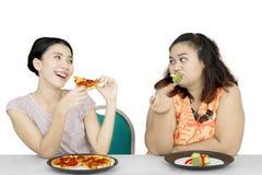 Beleibter Frauenblick auf Freund essen Pizza lizenzfreie stockfotografie