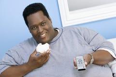 Beleibter Mann, der Donut hält Stockfotografie