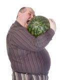 Beleibter Mann, der eine Wassermelone beißt Lizenzfreies Stockbild