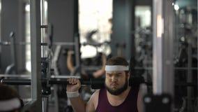 Beleibter Mann, der kaum Übung mit Barbell in der Turnhalle, Eignungstraining, Sport tut stock video
