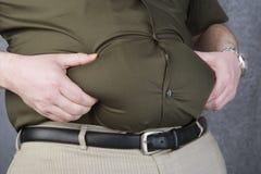 Beleibter Mann, der sein Fett auf dem Magen ergreift stockbilder